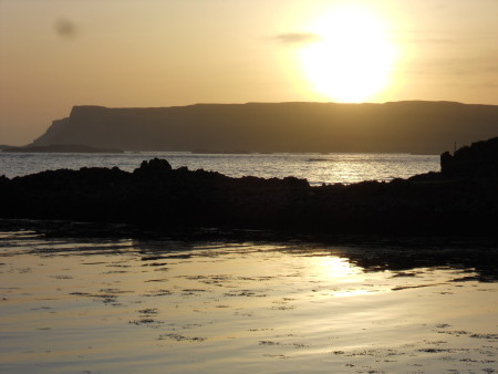 Pale gold sunset over the westernmost tip of the island, reflected in the sea