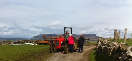 Lawrence McEwan on red tractor, isle of Eigg in the background under a blue sky
