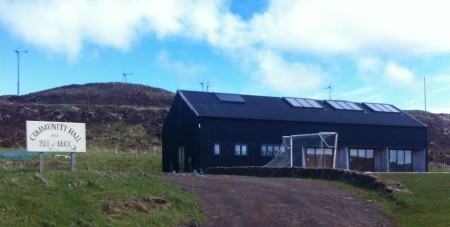 Timber built community centre, with windmills on the hill behind